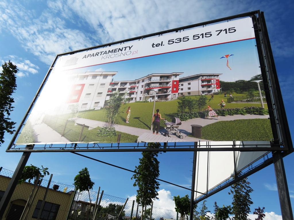 Baner reklamowy dla Apartamenty Krosno zawieszony na konstrukcji metalowej.