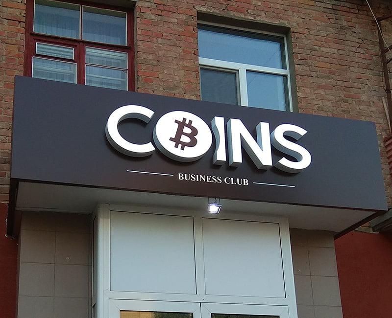 Szyld reklamowy czarny z przestrzennymi lterami podświetlanymi białymi Coins Studio Efekt